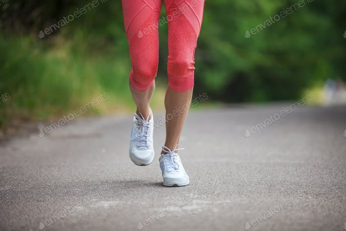 Cropped view of woman athlete running on pathway in park