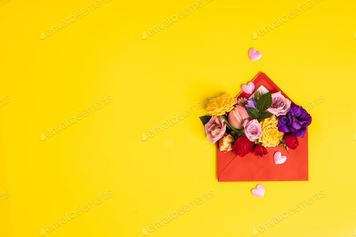Opened red envelope with flowers arrangements on yellow backgrou