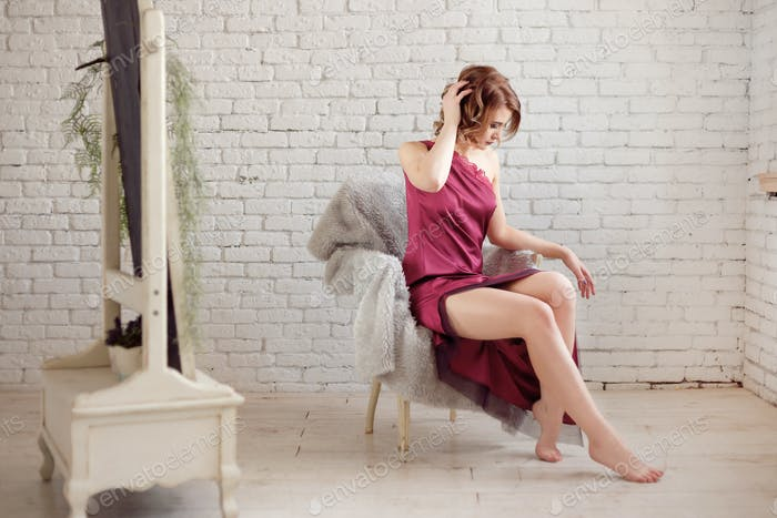 sensuality attractive woman with beautiful legs sits on white chair in loft interior