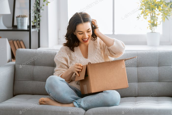 woman is holding cardboard box sitting on sofa at home