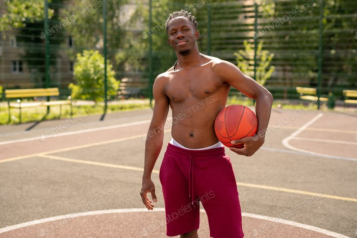 Young topless basketball player with ball standing on the court