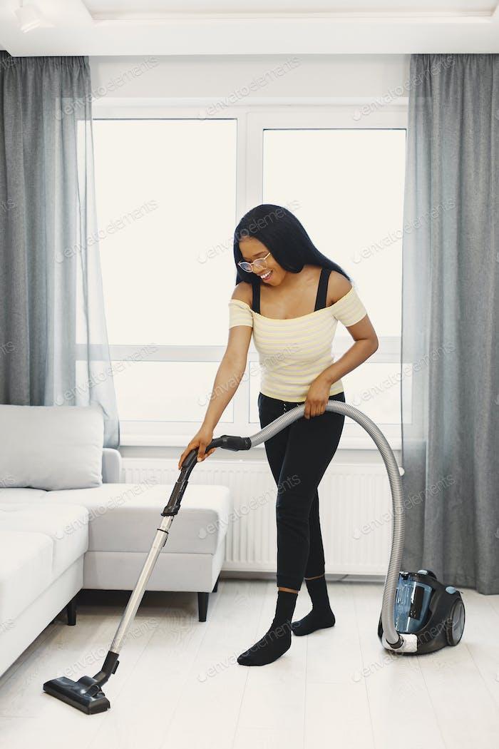 Mujer afroamericana usando aspiradora en casa