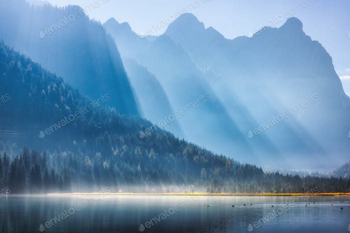 Majestic mountains in bright sunbeams and foggy lake at sunrise