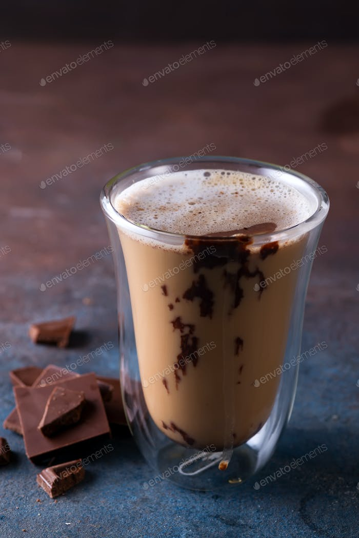 Glass cup of coffee latte with chocolate on stone dark table