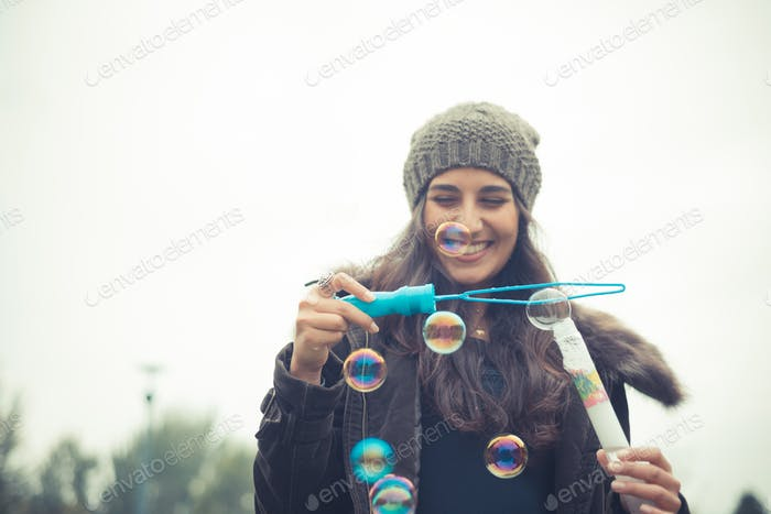 young beautiful brunette woman blowing bubble soap