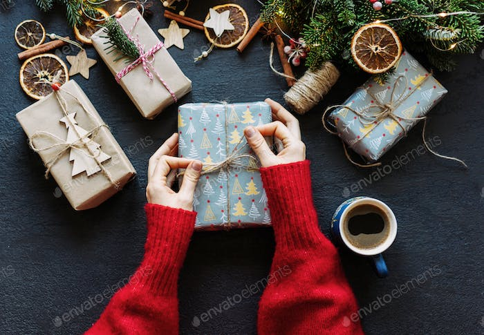 Elegant female hands tying twine on a wrapped Christmas present.  Festive layout