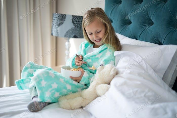 Lächelnd Mädchen Fütterung Frühstück Teady Bär auf Bett
