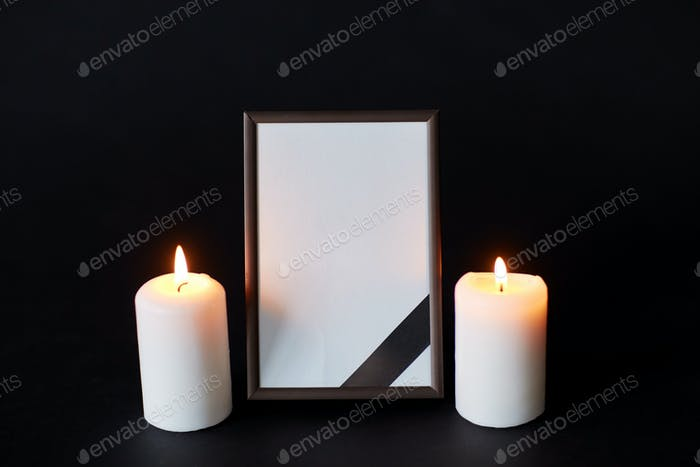 black ribbon on photo frame and candles at funeral