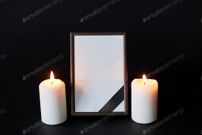 черная лента на фоторамке и свечах на похоронах