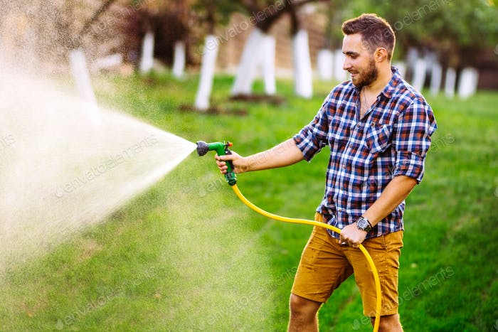 portrait of gardener using water hose and watering the lawn, grass and plants.