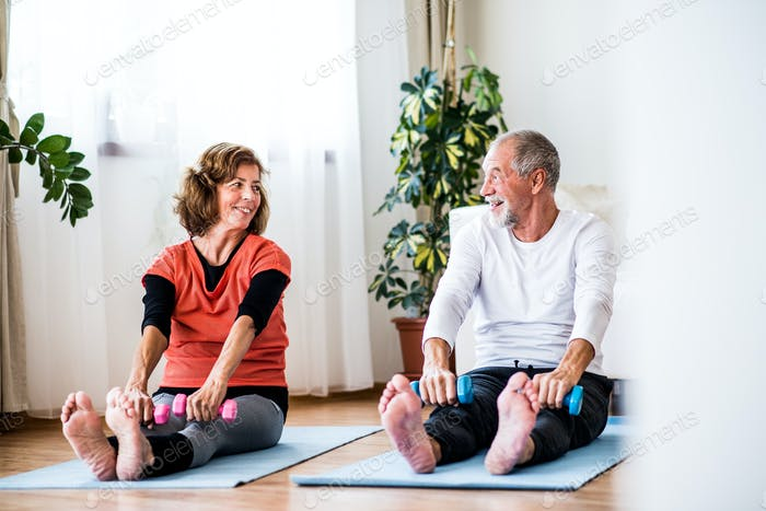 A senior couple with dumbbells doing exercise at home.