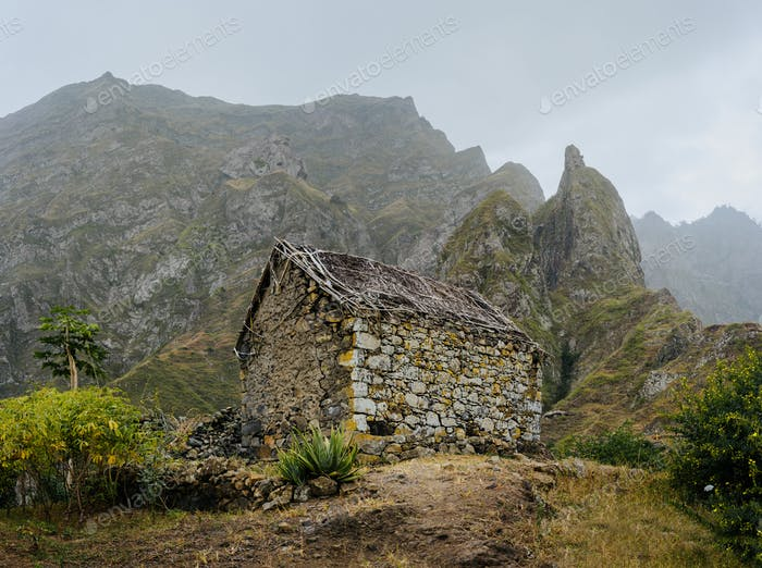 Ruined local storehouse nestled into incredible scenery with steep mountain rocks and vertical peaks