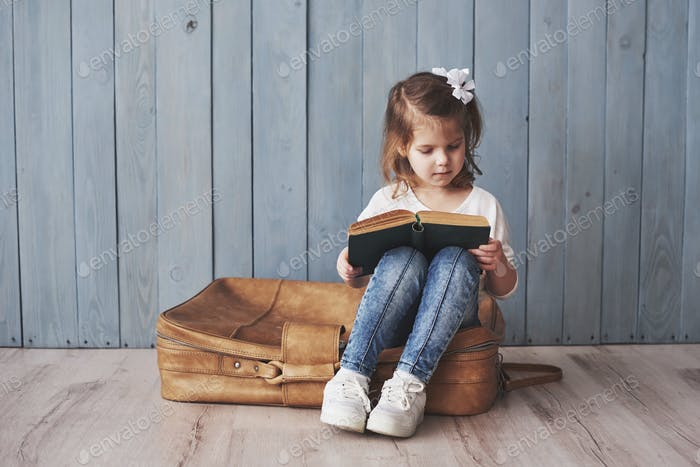 Glückliches kleines Mädchen lesen interessante Buch trägt eine große Aktentasche und lächelnd