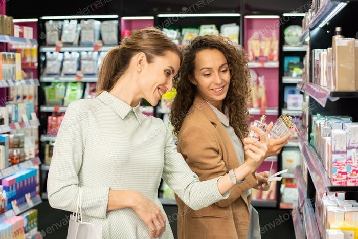 Two happy young female shoppers with bottles of scents choosing new fragrance