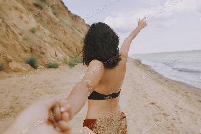Follow me. Woman leading her man, holding hands on beach