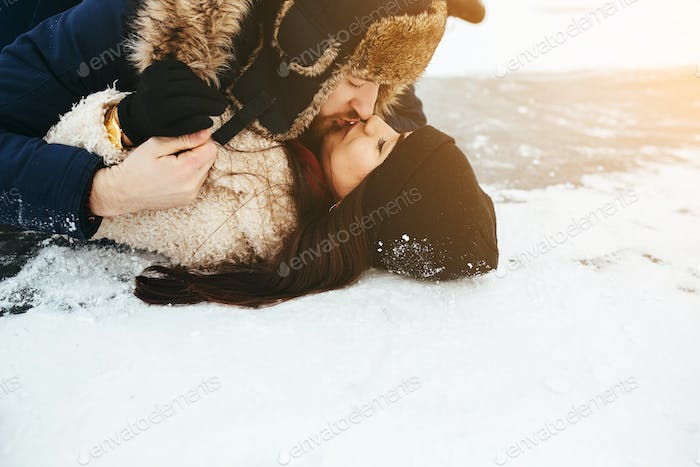 man and woman kiss on ice
