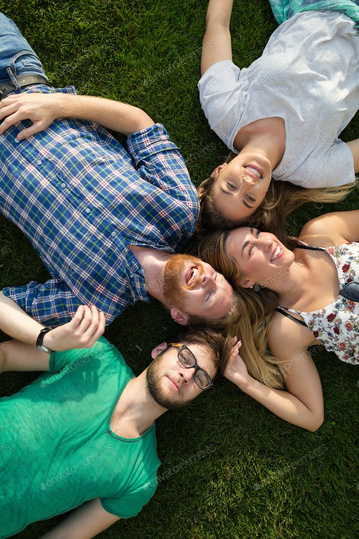 Happy students lying on ground and smiling