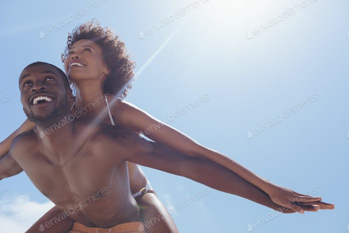 Man carrying woman piggyback at beach on a sunny day. They are smiling