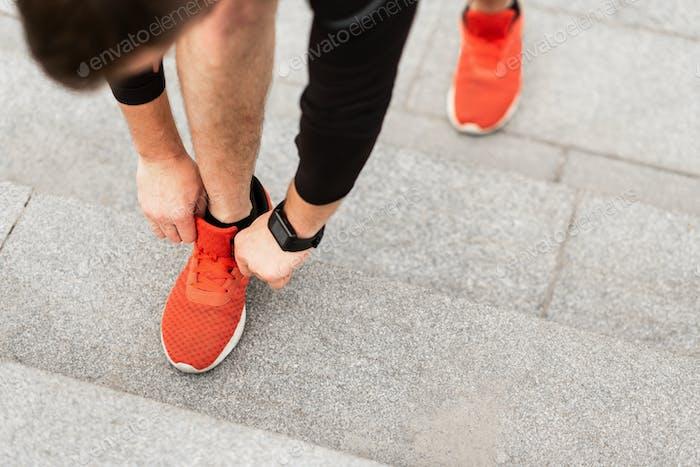 Closeup of Young Man Tying Sports Shoe