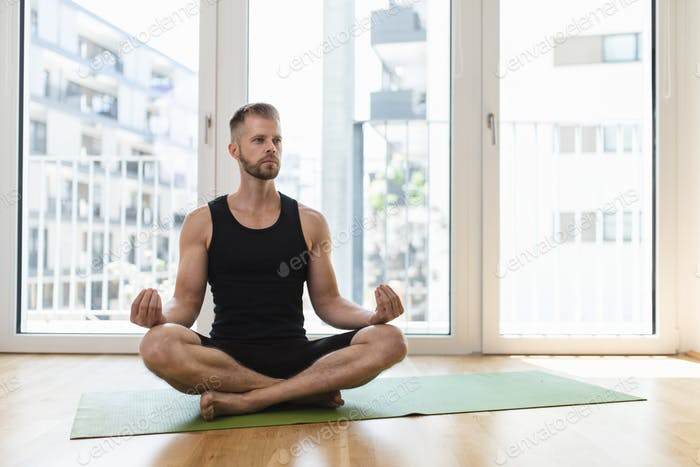 Man practicing yoga at his home
