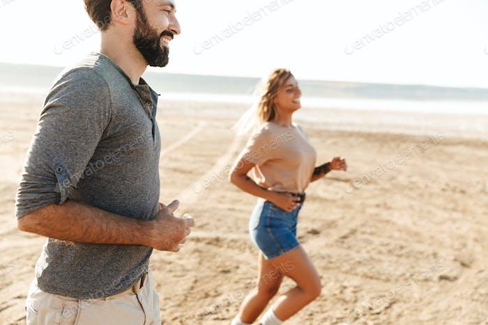 Fröhliches junges Paar läuft am sonnigen Strand