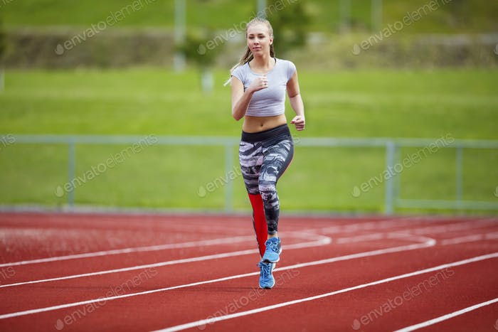 Woman In Sportswear Running On Sports Track