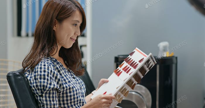 Asian woman at the hair salon, choose the color on book