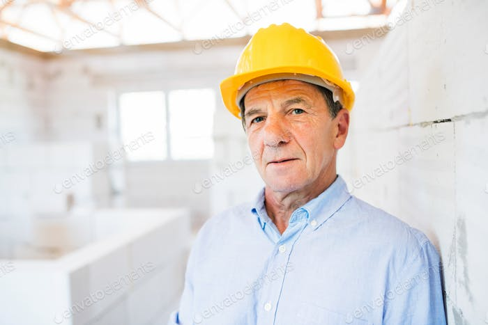 Senior architect or civil engineer on the construction site.