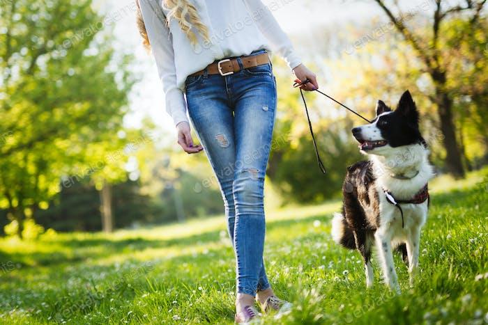 Schöne Frau zu Fuß niedlichen Hund in der Natur