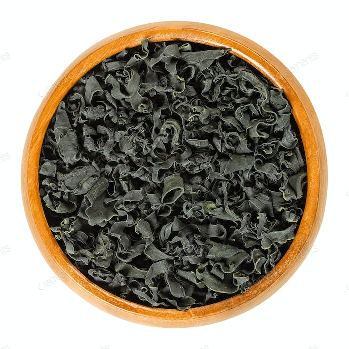Dried wakame, a seaweed, in wooden bowl over white