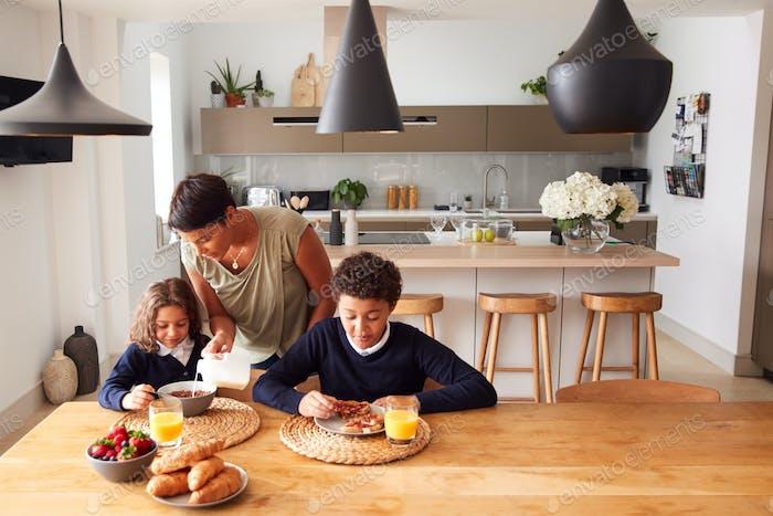 Mutter in der Küche helfen Kinder mit Frühstück vor der Schule