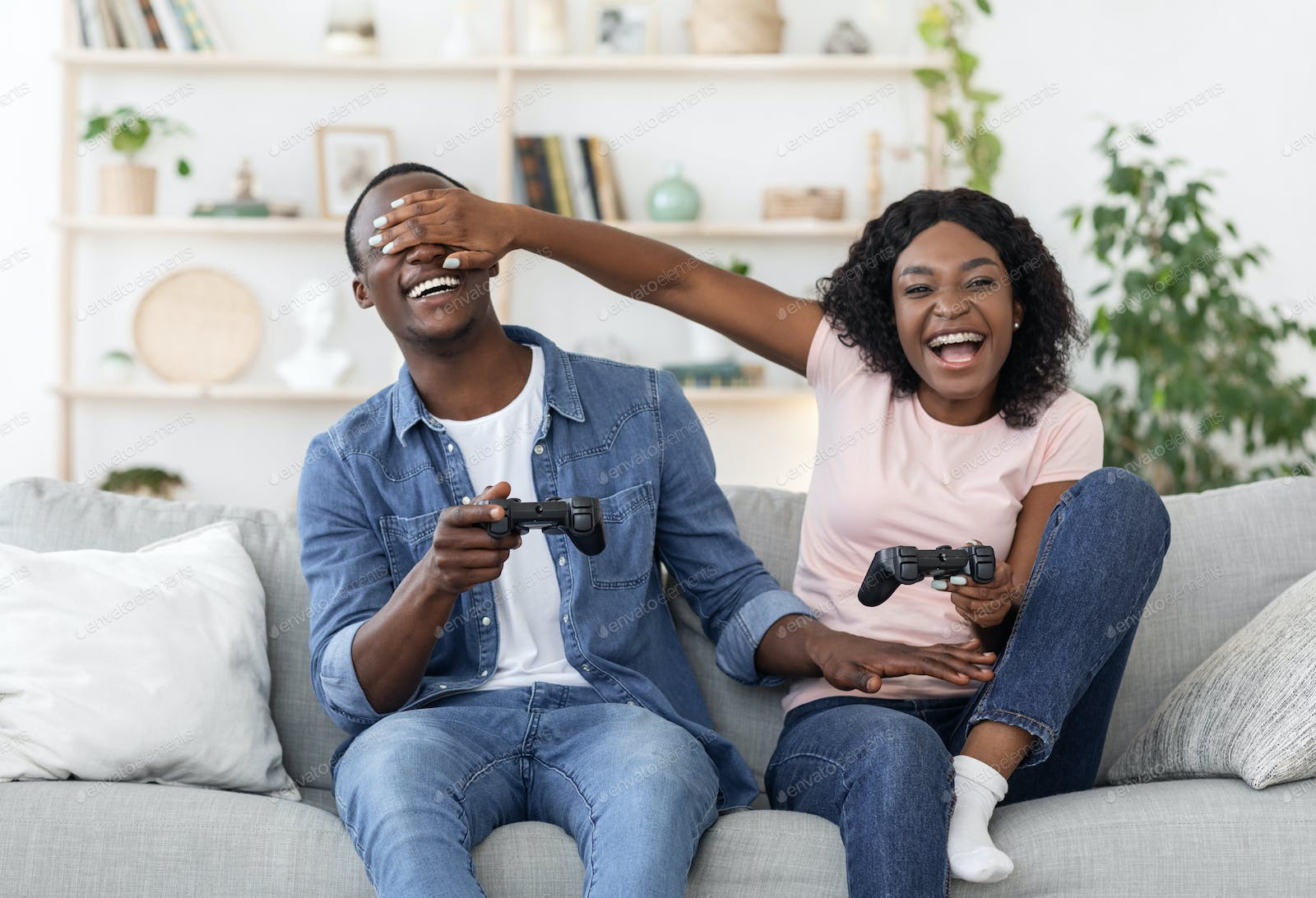 Happy black couple playing video game, woman covering boyfriend eyes photo  by Prostock-studio on Envato Elements