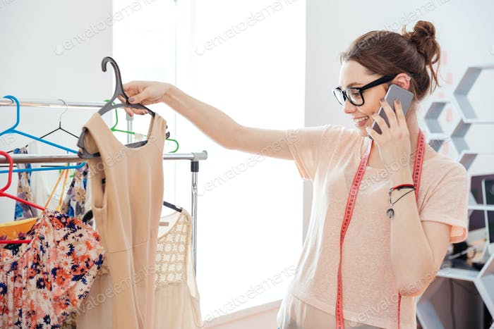 Woman fashion designer choosing dress and talking on mobile phone