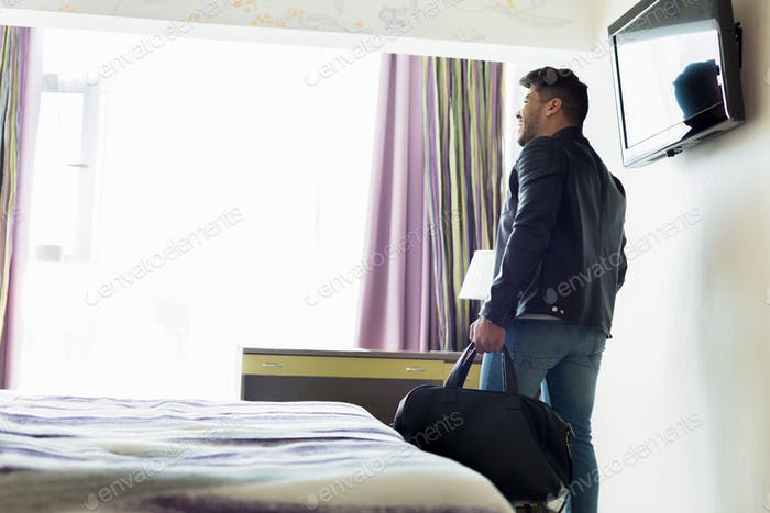 Young man with bag in hotel room