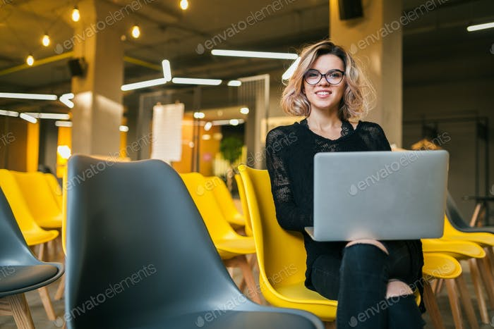 portrait of young attractive woman sitting in lecture hall working on laptop