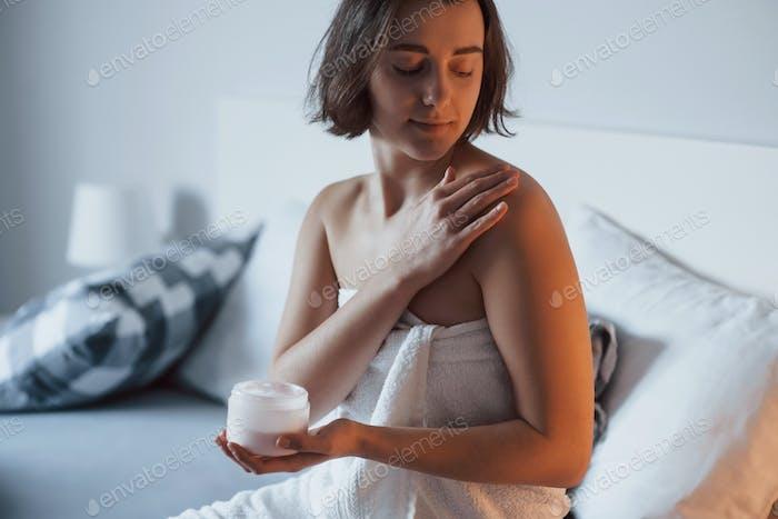Ruhig und ruhig. Zeit für ein Make-up. Frau sitzt auf dem Bett und verwenden Kosmetika, um ihre Haut zu reinigen