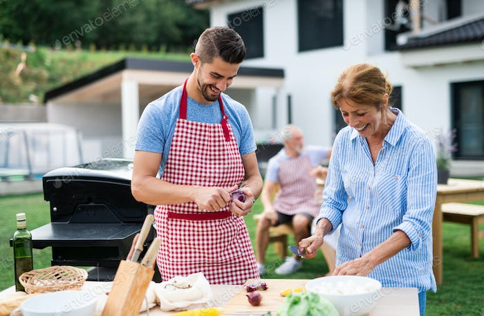 Portrait of multigeneration family outdoors on garden barbecue, grilling