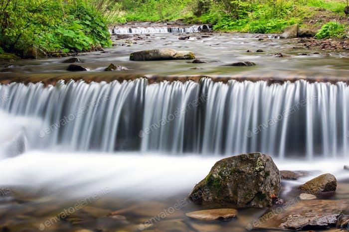 Kleiner Bach-Wasserfall auf Quellwald
