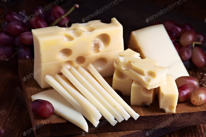 Pieces of cheese and bunches of grapes on wood illuminated with selective light