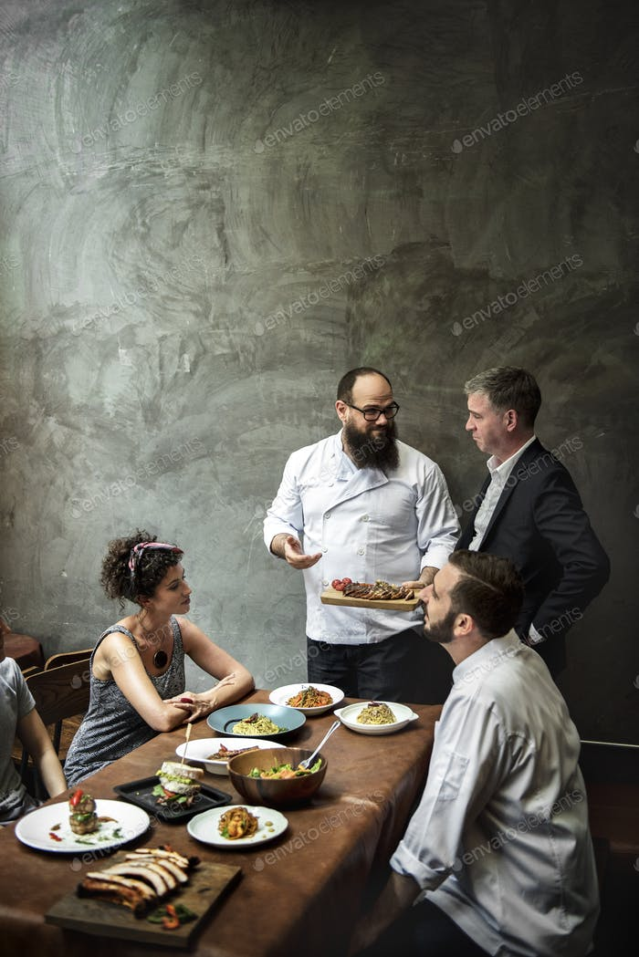 Chef presenting food to customers in the restaurant