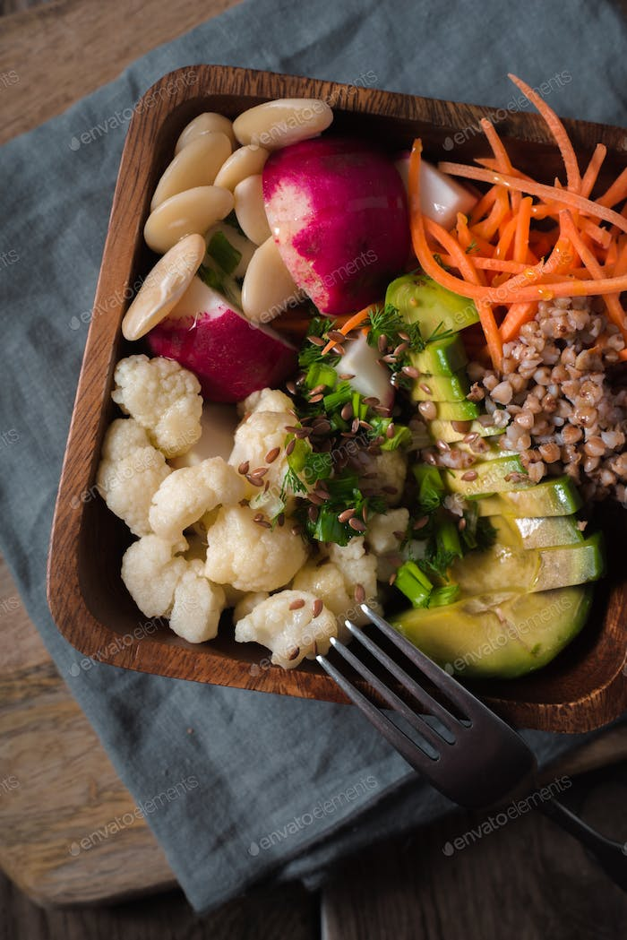 Salad with buckwheat and vegetables in a wooden bowl