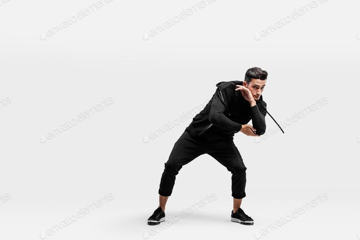 Handsome young man wearing a black sweatshirt and black pants is dancing breakdance