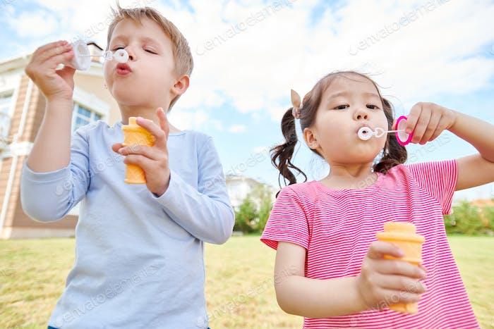 Happy Children Blowing Bubbles