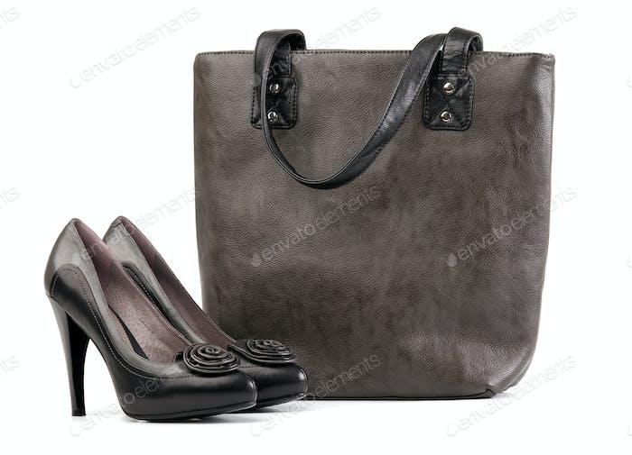 Paar schwarze Damenschuhe und Handtasche