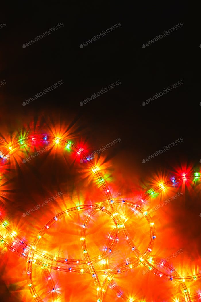 Colored light christmas garland illumination background on black, unfocused.