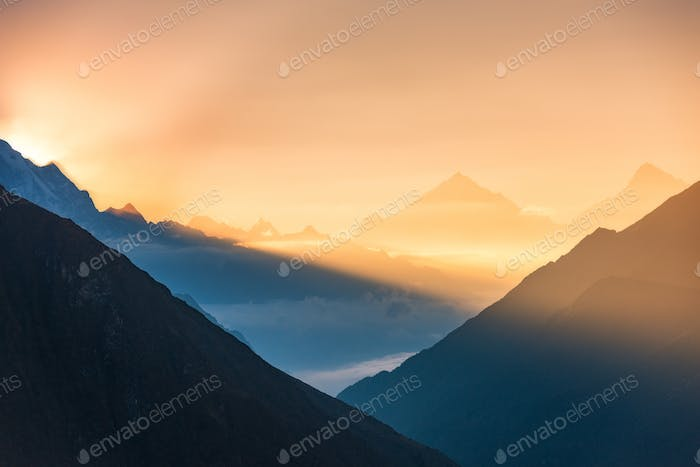 Mountains and low clouds at colorful sunrise in Nepal