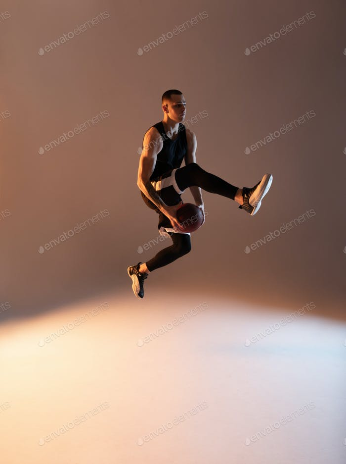 Athlete jumping with ball under leg