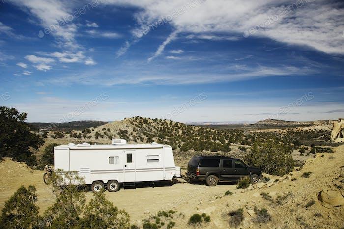 53788,Car pulling trailer in desert landscape, Grand Staircase Escalante, Utah, United States
