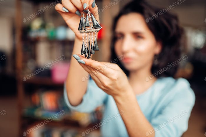 Female master with pliers making handmade earrings