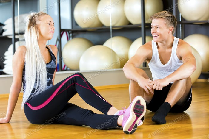Smiling Young Man And Woman Sitting In Gym
